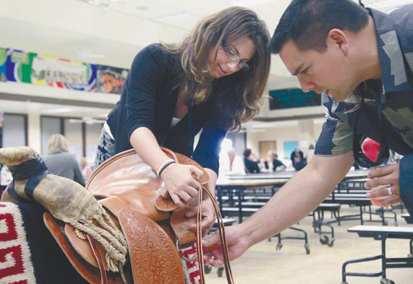 "King Kekaulike, then senior, Mary Klein shows volunteer judge Leo Caires a saddle she built for her 2013 senior project last year. Klein said she prepared rawhide and replaced an old saddle she found with new leather. ""I love it,"" she said. ""It's very comfortable and fits my horse."" The project took about 170 hours of work; she was mentored by leatherworkers Henry Silva and Gretchen Cardoso. The Class of 2013 members presented their individual senior projects to about 330 volunteer judges in classrooms across the campus. Photo & Story Courtesy:  The Maui News / CHRIS SUGIDONO"